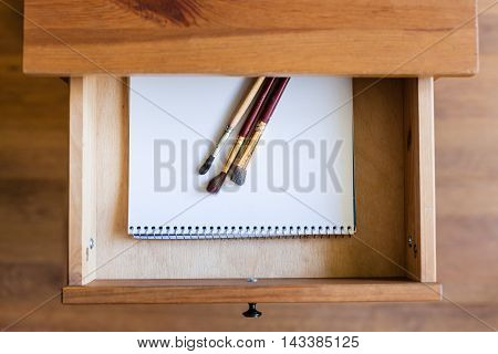 Painting Brushes On Drawing Album In Open Drawer