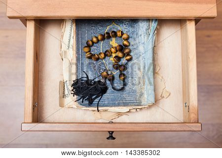 Rosary On Old Religious Book In Open Drawer