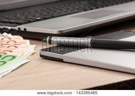 Working businessman deskstylus pen tablet money as the background view from above