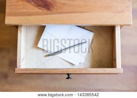 Folded Sheet Of Paper And Pen In Open Drawer