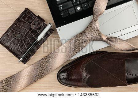 Fashion and business notebook shoes and tie on a wooden table as background top view