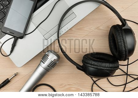 Laptop microphone headsets lies on a wooden table background top view