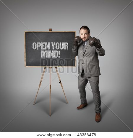 Open your mind text on  blackboard with businessman wearing boxing gloves