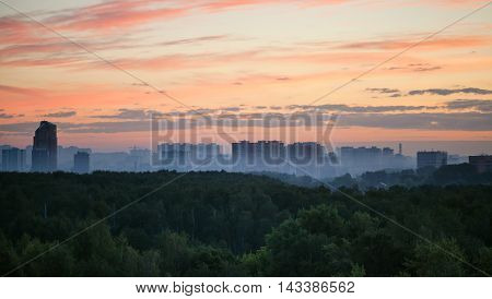 Early Sunrise And Morning Mist Over Woods And City