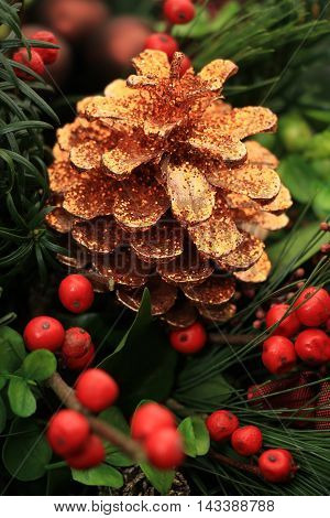 Golden pine cone and red berries in a Christmas centerpiece