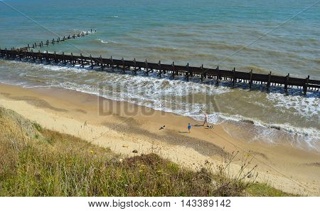 CORTON, SUFFOLK, ENGLAND - AUGUST 17, 2016: People walking on beach between failing sea defenses  and crumbling cliffs.