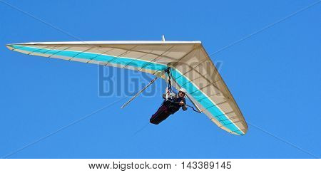 CORTON, SUFFOLK, ENGLAND - AUGUST 17, 2016: Blue and white hang glider with blue sky background.