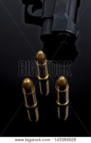 Gold bullets and gun on black background