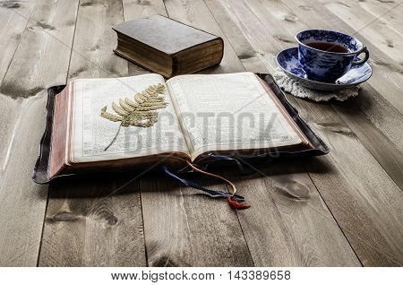 Peaceful religious scene of open and closed vintage Bibles on wooden table with cup and saucer of tea. Bibles are non trademark version.
