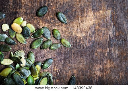 Pumpkin seeds over wooden table with copy space