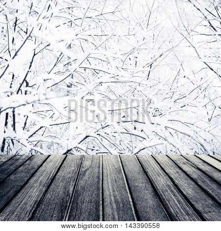 Abstract Christmas background. Beautiful wood board table in front of Christmas tree branches with white snow