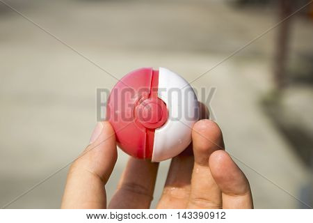 Thailand - August 20, 2016: Poke ball in Hand  (Pokemon Ball). Pokeball toy of the game Pokemon Go at Chon Buri, Thailand.