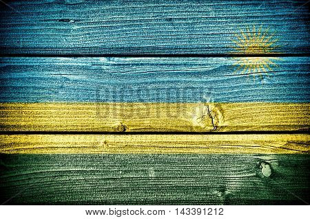 flag of Rwanda painted on old grungy wooden background: 3d illustration