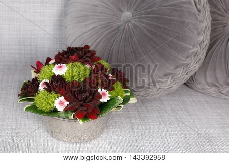 Dark red and green floral centerpiece on gray background
