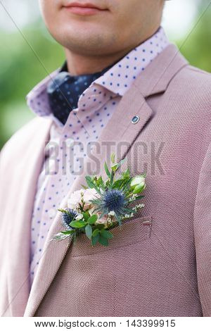 Pink and blue boutonniere on pink suit of the groom
