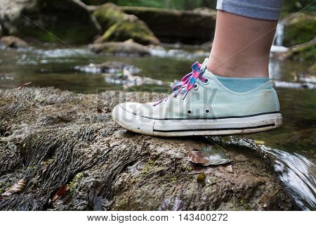 Girls Foot Stepping On A Mossy Rock