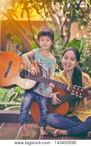 Happy family spending time together with bright sunlight at home. Asian mother with daughter smiling and playing classic guitar. Positive human emotion. Vintage tone effect.