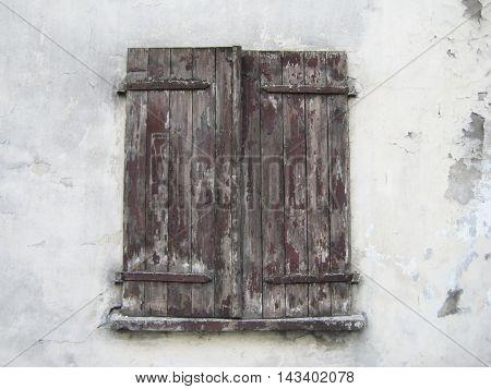 Old dark brown window shutters on vintage white wall