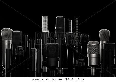 Set of different microphones against black background