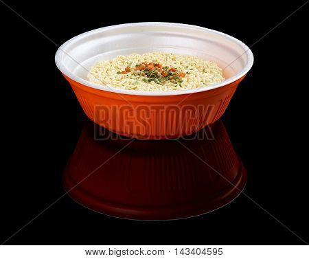 Instant noodles in plastic plate isolated on black reflecting background