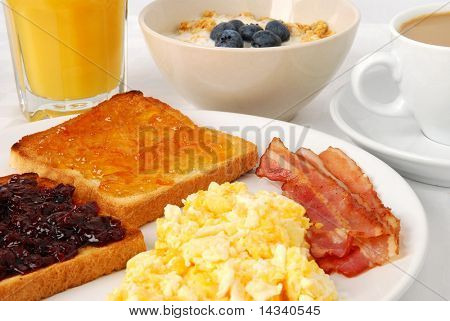 Breakfast with scrambled eggs, bacon and toasts with jam