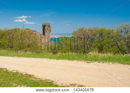 Spring landscape with earth road near Devil Finger crag in Karadag National park Crimean peninsula