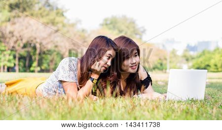 Young pretty woman with laptop lying in a park