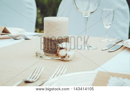 Stylish winter decor twine candle with cotton flower on craft background. Wedding table setting with elegant cutlery napkin and glass. Rustic style. Lovely floral detail decoration. Rustic style. Text copyspace.