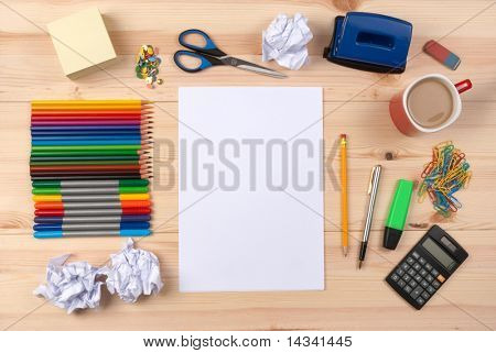 Escritorio con hoja de papel y artículos de papelería objetos vistos desde arriba