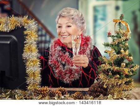 Stunning aged woman sits at the desk with glass of dry wine in her hand. Senior woman raises online toast looks at decorated monitor with silver yellow tinsel garland. There are small Christmas tree, pine cones, keyboard on the desk