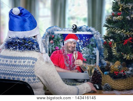 Mature fat man in Santa Claus costume wishes one of his female helper a Merry Christmas and offers a toast with white sparkling wine during online video session. Woman in blue hat with white pigtails sits at the desk and looks at monitor