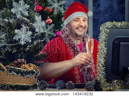 Cheerful middle-aged man in Santa Claus costume toasting glass of white sparkling wine in front of monitor. Bearded fat man sits at the desk surrounded tinsel garlands, balls, snowflakes, pine cones. He looks at the monitor his face illuminated by the scr