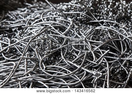 Aluminum turning metal.Heap with waste of silver twisted metal shavings in closeup.