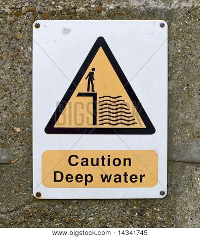 yellow and black caution deep water sign on wall
