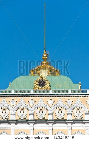 Fragment of facade of the Grand Kremlin Palace with the coats of arms of Russia and chimes