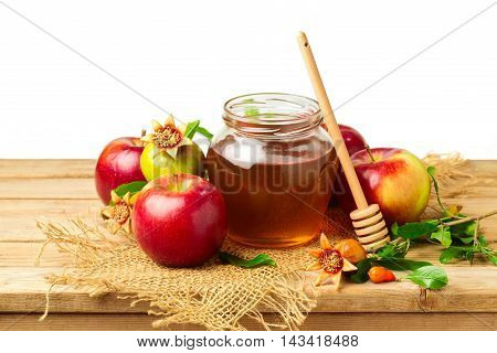 Honey apple and pomegranate on wooden table over white background