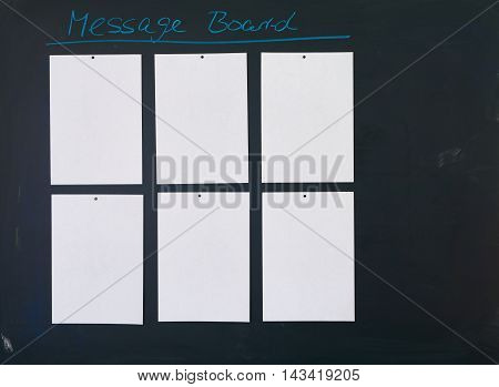 Black chalkboard as Message Board with six empty white sheets of paper attached to it.