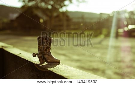 Cowboy boot on a wooden fence with a sun ray and ranch background