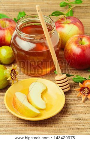 Honey with wooden stick and apples with pomegranate