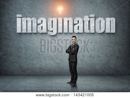 Businessman stands with his arms folded with big 3d 'imagination' word above. Ideas and concepts. Business staff. Office clothes. Intelligence and creativeness.