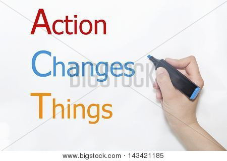 Action Changes Things written by hand with blue marker on whiteboard.