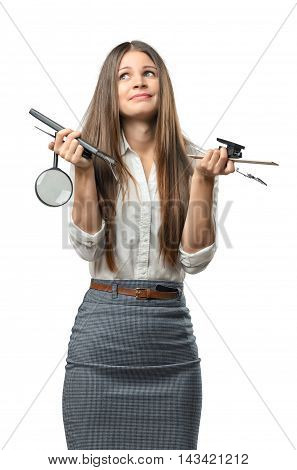 Confused young businesswoman holding office stationery isolated on white background. Business staff. Troubles and problems at work. Searching for solutions.