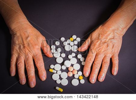 The old female hands with pills on black background