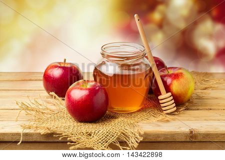 Apples with honey jar on wooden table over bokeh background