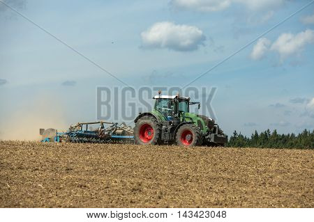Green Tractor with cultivator handles field before planting
