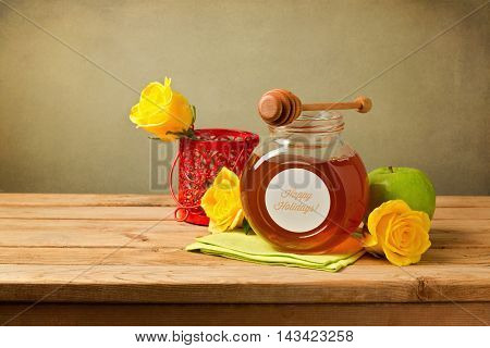 Honey apple and flowers on wooden table. Jewish New Year celebration.