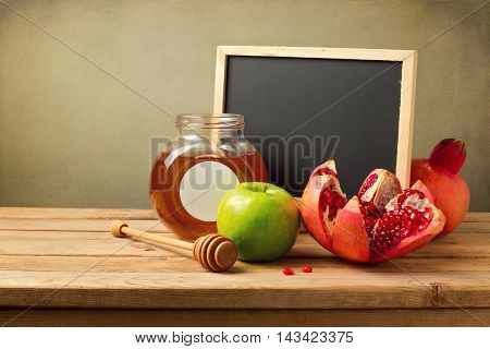 Honey apple and pomegranate with empty chalkboard