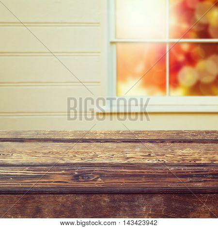 Empty wooden table over window background for product placement