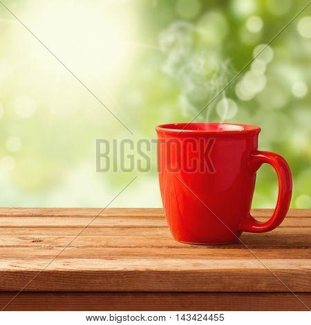 Coffee mug over garden bokeh on wooden table