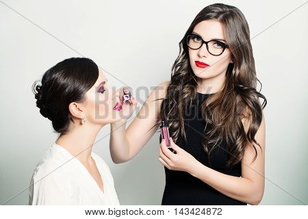 Make-up Artist Girl Applying Lip Gloss. Fashion Beauty Background